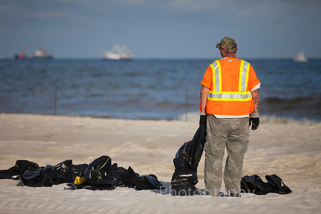 A lone clean up worker watches as skimmers ply the offshore waters in response to the BP Deepwater Horizon oil leak. Baldwin County, Alabama. June 2010.