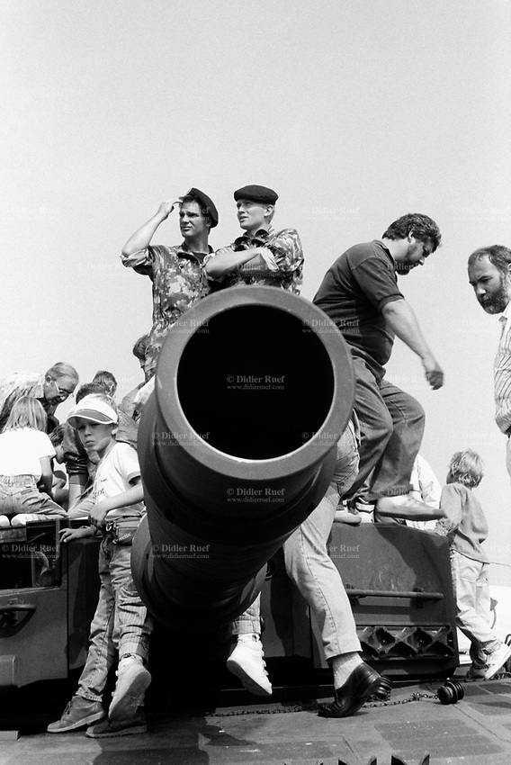Switzerland. Canton Lucerne. Emmen. Military parade. Soldiers, tank's barrel and spectators. © 1991 Didier Ruef