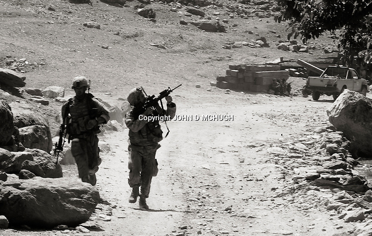 US Embedded Tactical Trainer (ETT) SGT Clark (L) and Master Sergeant Best run for cover while under fire during an ambush near Kamu outpost in Nuristan Privince, north-east Afghanistan, 14 May 2007. Elements of White Platoon were called upon, along with US Embedded Tactical Trainers (ETTs) and ANA from 1st Company, 2nd Kandak, 201st Corps, Afghan National Army, to act as a Quick Reaction Force to a nearby earlier ambush, but minutes after coming accross the first of the dead and wounded they were engaged by insurgents heavily dug into the mountainsides and got caught up in a major firefight. By the end of the day there were 15 ANA dead, 4 wounded, and one believed captured by insurgents. 6 US personnel and 1 Irish photographer were also wounded during the fight. (John D McHugh)