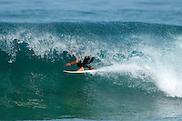 A male surfer gets barrelled inside a wave while surfing.