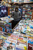 India, Dehradun.  News Stand Attendant at the Dehradun Train Station on a Cold Winter Morning.