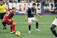FOXBOROUGH, MA - SEPTEMBER 21: Carles Gil #22 of New England Revolution passes the ball  as Sebastian Saucedo #23 of Real Salt Lake comes in to tackle during a game between Real Salt Lake and New England Revolution at Gillette Stadium on September 21, 2019 in Foxborough, Massachusetts.
