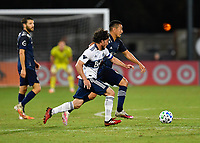 LAKE BUENA VISTA, FL - JULY 26: Russell Teibert of Vancouver Whitecaps FC pressures Roger Espinoza of Sporting KC during a game between Vancouver Whitecaps and Sporting Kansas City at ESPN Wide World of Sports on July 26, 2020 in Lake Buena Vista, Florida.