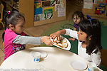 Preschool 3-4 year olds meal time one girl offering another a plate of bagels