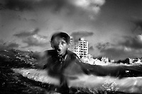 13 year old surfer Momen Abu Assi battles with the waves in the Mediterranean Sea as he practises surfing.
