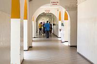 Dakar, Senegal.  Dakar Hospital, Corridor and Receding Arches.  Nurse Watching Family Members Depart.