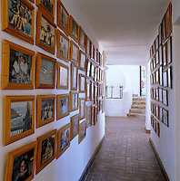 Framed family photographs line the walls of the corridor