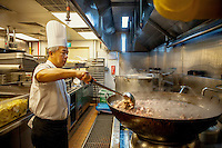 A chinese chef in the kitchen of the Marina Bay Hotel. The kitchen prepares Western, Chinese and Halal food simultaneously in three different sections.