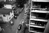 """Switzerland. Canton Ticino.  Viganello. Viganello is a quarter of Lugano. Rainy day on Via Muggina. Cars parked on the road. Lonely people with umbrellas walk on sidewalks. Due to the spread of the coronavirus (also called Covid-19), the Federal Council has categorised the situation in the country as """"extraordinary"""". It has issued a recommendation to all citizens to stay at home, especially the sick and the elderly. From March 16 the government ramped up its response to the widening pandemic, ordering the closure of bars, restaurants, sports facilities and cultural spaces. Only businesses providing essential goods to the population – such as grocery stores, bakeries and pharmacies – are to remain open. 20.04.2020 © 2020 Didier Ruef"""