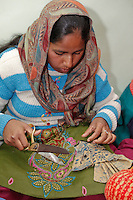 Dehradun, India.  Muslim Indian Woman Working with Fabric in Women's Sewing Instruction Class.
