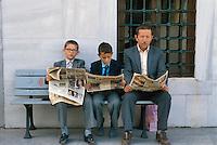 - father and two children read the newspaper in the Topkapi palace garden ....- padre e due bambini leggono il giornale nei giardini del palazzo Topkapi
