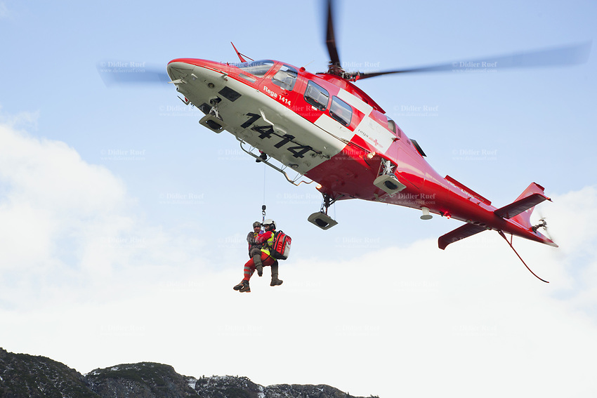 """Switzerland. Canton Grisons. Lai da Marmorera (Marmorera Stausee). A Rega Agusta AW109 SP Grand """"Da Vinci"""" helicopter has rescued a swiss german hunter with an broken shoulder. By using a rescue hoist, a helicopter can rescue persons from hard-to-reach areas in the Alps. The Vertical Rescue Triangular Harness secures the emergency physician, Doctor Alessandro Genini and the patient during a lift. The Vertical Rescue Triangular Harness is a simple yet robust patient lifting sling designed for all forms of rapid vertical extrications.The simple design allows the harness to be applied to the patient easily and quickly compared to other full body rescue harnesses. All Rega helicopters carry a crew of three: a pilot, an emergency physician, and a paramedic who is also trained to assist the pilot for radio communication, navigation, terrain/object avoidance, and winch operations. The name Rega was created by combining letters from the name """"Swiss Air Rescue Guard"""" as it was written in German (Schweizerische Rettungsflugwacht), French (Garde Aérienne Suisse de Sauvetage), and Italian (Guardia Aerea Svizzera di Soccorso). Rega is a private, non-profit air rescue service that provides emergency medical assistance in Switzerland. Rega mainly assists with mountain rescues, though it will also operate in other terrains when needed, most notably during life-threatening emergencies. As a non-profit foundation, Rega does not receive financial assistance from any government. People in distress can call for a helicopter rescue directly (phone number 1414). The AgustaWestland AW109 is a lightweight, twin-engine, helicopter built by the Italian manufacturer Leonardo S.p.A. (formerly AgustaWestland, Leonardo-Finmeccanica and Finmeccanica). Leonardo S.p.A is an Italian global high-tech company and one of the key players in aerospace. In close collaboration with the manufacturer, the Da Vinci has been specially designed to cater for Rega's particular requirements as regards carrying ou"""