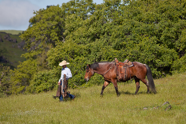 Ranch hand carrying gear and walking his horse down a hill