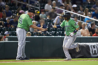 Gwinnett Braves manager Damon Berryhill (55) slaps hands with Andres Blanco (13) as he rounds third base after hitting a home run against the Charlotte Knights at BB&T BallPark on July 12, 2019 in Charlotte, North Carolina. The Stripers defeated the Knights 9-3. (Brian Westerholt/Four Seam Images)