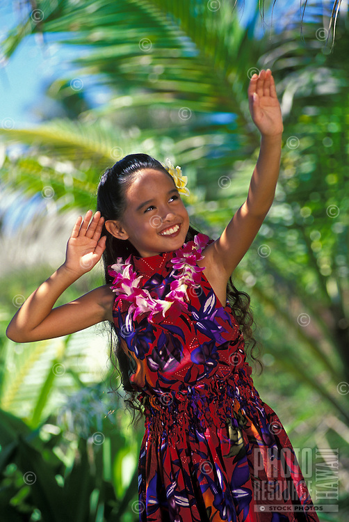 Beautiful Young Hawaiian girl dancing an aunana (modern) hula with an orchid lei and plumeria flower in her ear