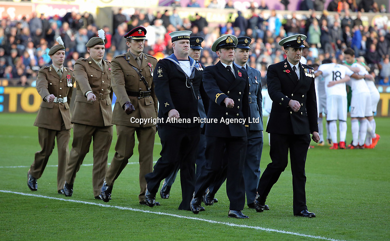Members of the armed forces parade off the pitch l during the Premier League match between Swansea City and Brighton and Hove Albion at The Liberty Stadium, Swansea, Wales, UK. Saturday 04 November 2017