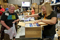 Penny Kuello (right), a regular volunteer, opens boxes of non perishable food items Monday, June 7, 2021, for distribution at the Northwest Arkansas Food Bank in Springdale. For more information about the Northwest Arkansas Food Bank and opportunities to volunteer visit nwafoodbank.org. Check out nwaonline.com/210608Daily/ and nwadg.com/photos for a photo gallery.<br /> (NWA Democrat-Gazette/David Gottschalk)