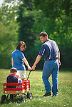 parents pulling children sitting in toy wagon at park