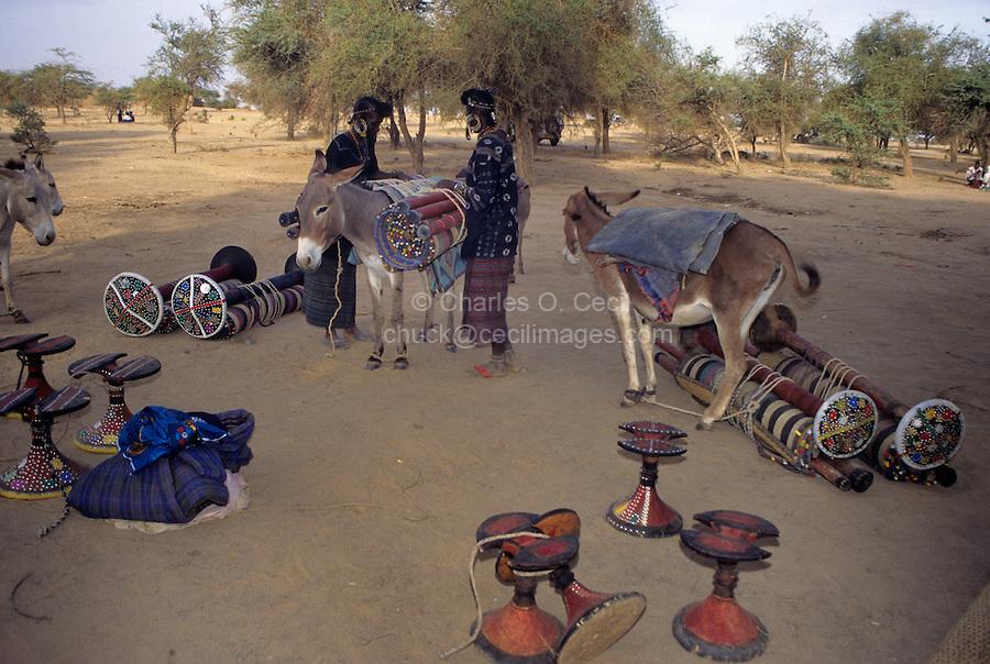 Akadaney, Central Niger, West Africa.  Fulani Nomads.  Women Loading Portable Bed Pieces on Donkey.