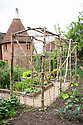 Home-made frame for supporting climbing plants in vegetable garden at Tidebrook Manor, East Sussex, early June.