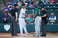 Chicago White Sox video technician Jack Larimer shakes hands with Greensboro Grasshoppers manager Kieran Mattison (24) as umpires Joe Belangia (left) and Dylan Bradley look on at Truist Stadium on August 13, 2021 in Winston-Salem, North Carolina. (Brian Westerholt/Four Seam Images)