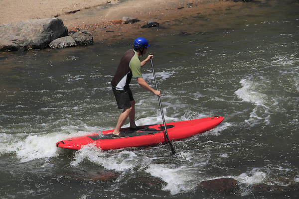 Man on stand-up paddle board at Boulder Creek, Boulder, Colorado. .  John offers private photo tours in Denver, Boulder and throughout Colorado. Year-round.