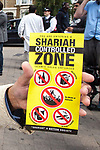 """© Joel Goodman - 07973 332324 . 30/07/2011 . London , UK. Shariah controlled zone flyers . Islamist group, Muslims Against Crusades, march through Waltham Forest in East London, calling for Sharia law to be imposed in the UK. MAC supporters carried """" Shariah Controlled Zone """" stickers, that have been appearing in parts of East London which have caused concern to some residents. Photo credit : Joel Goodman"""