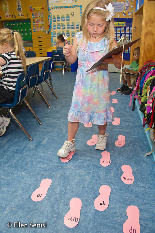 MR / Schenectady, NY. Zoller Elementary School. Kindergarten. Student (girl, 5) does a sight word activity during learning center time. Sight words are written on cards shaped as feet. As she steps on each word, she writes it down on her worksheet. MR: Gui5. ID: AL-gKs. © Ellen B. Senisi