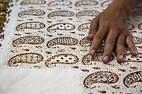 Yogyakarta, Java, Indonesia.  Batik Workshop.  Male Worker Applying Block Design to Batik Fabric.