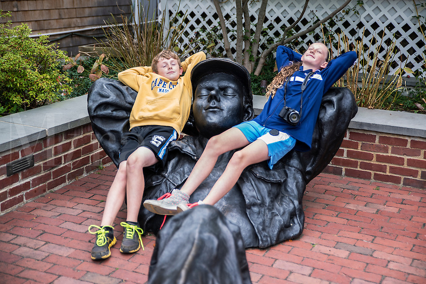 Siblings relax with a sculpture, Edgartown, Martha's Vineyard, Massachusetts, USA