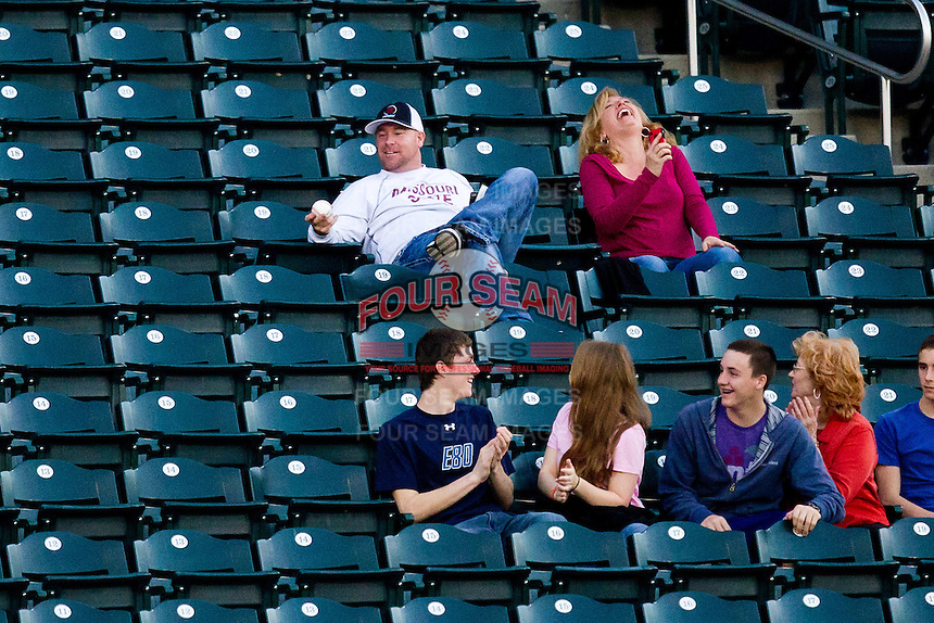 A fan examines the foul ball he caught after a one handed grab as his wife laughs at him during a game between the Purdue Boilermakers and the Missouri State Bears at Hammons Field on March 13, 2012 in Springfield, Missouri. (David Welker / Four Seam Images).