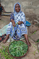 Mkokotoni, Zanzibar, Tanzania.  Woman with Sweet Potato Greens.  Her dress and scarf are made of kitenge cloth.