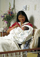 HAWAIIAN AMERICAN MOTHER WITH HER NEWBORN BABY IN PRIVATE HOSPITAL ROOM. MOTHER AND NEWBORN. BERKELEY CALIFORNIA.