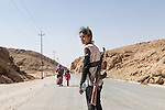 12/08/2014 -- Sinjar mountains, Iraq -- Runak Bapir Gherib, 14 y.o. from Shengal makes her way down the mountain after 7 days. She is with her mother and sister (in the back) waiting for a car to drive them away. She took the gun from Shengal to protect her family. YPG also gave weapons to the people who wanted to fight, but it has been impossible to verify whether this weapon was given to her by YPG or family members.