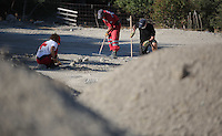 Pictured: Forensics officers and Hellenic Red Cross volunteers sift through soil in Kos, Greece. Thursday 06 October 2016<br />