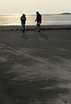 A young couple on the beach at West Kirby Wirral during a late Autumn afternoon.
