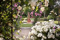 Terra cotta water fountain in lawn by rose garden.