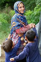 SERBIEN, 08.2016, Kelebija. Internationale Fluechtlingskrise: An der mit Zaeunen abgesperrten ungarischen Grenze stauen sich Fluechtlinge und Migranten. Sie bitten meist vergebens um Einlass in die  Asyl- und Transitzonen (blaue Container). So haben sich auf serbischer Seite provisorische Lager mit sehr schlechten Bedingungen gebildet. | International refugee crisis: Refugees and migrants have been piling up at the fenced-off Hungarian border. They are waiting for entrance into the asylum and transit zones (blue containers), mostly in vain. Thus provisional camps have emerged on the Serbian side with very bad conditions. In the picture Noor Mahmud with her sons Ali and Achmed.<br /> © Szilard Vörös/EST&OST