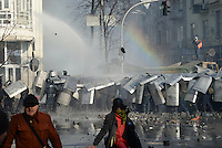 Riot police in the testudo formation protects from paving stones hailing. Kiev, Ukraine
