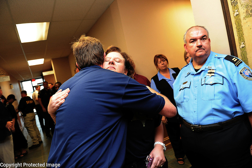 St. John the Baptist Parish Sheriff's Department employees console each other at a press conference after an early morning shooting at a Steel plant parking lot left two police officers dead and at least two civilians injured in Laplace, Louisiana August 16, 2012.  REUTERS/Cheryl Gerber  (UNITED STATES)