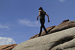 Young woman on slickrock in Arches National Park, Utah, USA. .  John offers private photo tours in Arches National Park and throughout Utah and Colorado. Year-round.