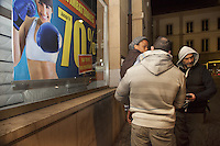 """Switzerland. The Republic and Canton of Neuchâtel. Neuchâtel. Downtown. Narcotics squad. """"Narko"""" operation. The commissar Manuel Garcia (R) and a police officer (both in plain-clothes) holds and handcuffed a convict man. The black man is arrested for selling illegal drugs in the streets. The inmate is an african man from Western Africa. Plainclothes law enforcement is a method used by police. The policemen wear plainclothes or """"ordinary clothes"""" instead of a uniform in order to avoid detection or identification as law enforcement agents. Police officers in plainclothes must identify themselves when using their police powers. A shop selling mattresses is offering a 70 percent discount to his customers. A smiling woman with blue boxing gloves on the shop window's advertising poster. 27.03.15 © 2015 Didier Ruef"""