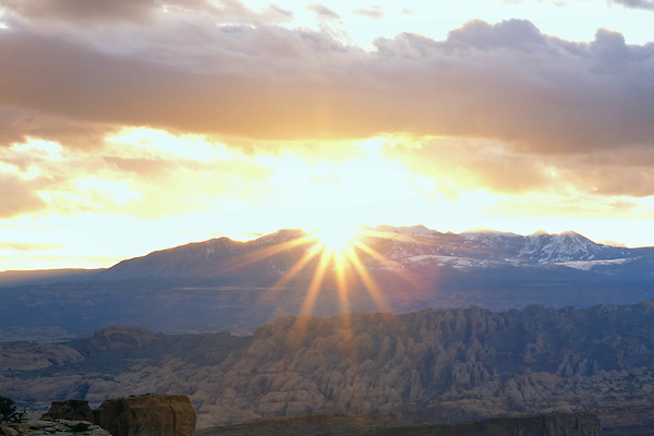 Sun setting behind the La Sal Mountains with slickrock formations, Island in the Sky area, Canyonlands National Park, Moab, Utah, USA.