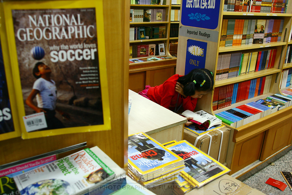 CHINA. Beijing. A girl reading books in a book store in the Wangfujing shopping district in central Beijing. 2006.