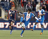 Philadelphia Union defender Sheanon Williams (25) attempts to control the ball as New England Revolution midfielder Diego Fagundez (14) pressures.In a Major League Soccer (MLS) match, the New England Revolution (blue/red) defeated Philadelphia Union (blue/white), 2-0, at Gillette Stadium on April 27, 2013.
