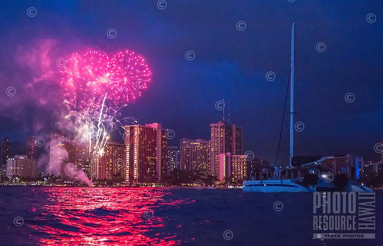 Fireworks over Hilton Hawaiian Village from the ocean near a catamaran cruise, Waikiki, Oahu