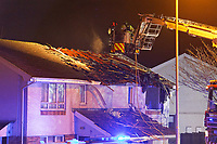 Pictured: Fire service personnel assess the damaged building in the Waunceirch area of Neath, Wales, UK. Monday 14 January 2018<br /> Re: Four flats have been evacuated after an explosion in Neath at 8:30pm on Monday.<br /> Extensive damage was caused to Waun Las, in the Waunceirch area and arrangements made to house its residents until the building is deemed safe.<br /> One woman was taken to hospital with serious burn injuries which are not believed to be life threatening.<br /> A joint investigation is under way between South Wales Police and the fire service to determine the cause.<br /> Wales and West Utilities said the gas supply to the affected property had been isolated.