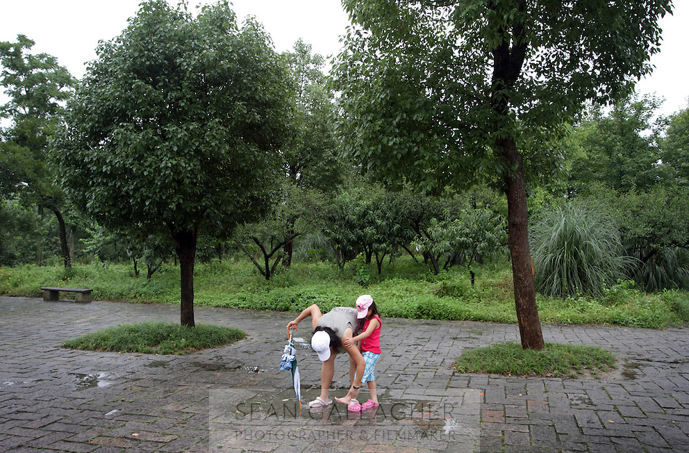 A mother and child in the Xixi wetlands which lie in the west of the city of Hangzhou. This is China's 'first national wetland park,' dubbed as such to act as a role model to all other wetlands in China and to supposedly show how to effectively manage and restore wetlands, notably urban wetlands. Zhejiang Province. China. 2010