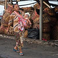 Bali, Indonesia.  Woman Carrying Baby in a Shoulder-sling.  Jimbaran.