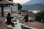 A Japanese couple taking pictures of themselves with Sakurajima behind while they put their feet on Ashi Yu, hot spring for feet.<br />